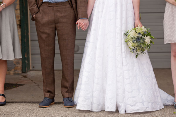 brown custom suit and white floral wedding gown