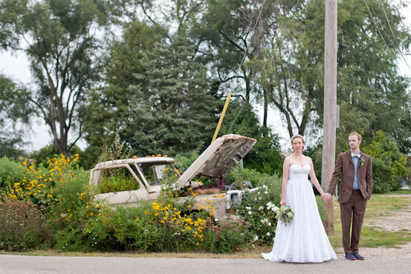 newlyweds Brian West and Sarah Ervin in front of a flower-covered pick-up truck
