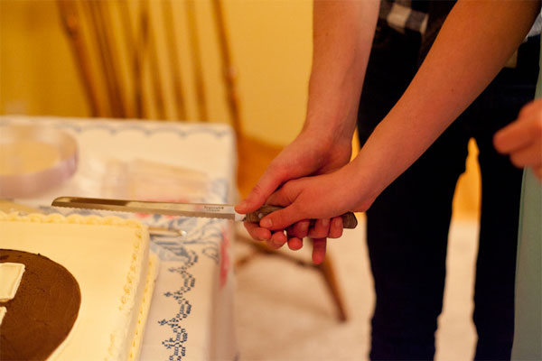Brian West and Sarah Ervin cutting their rehearsal dinner cake