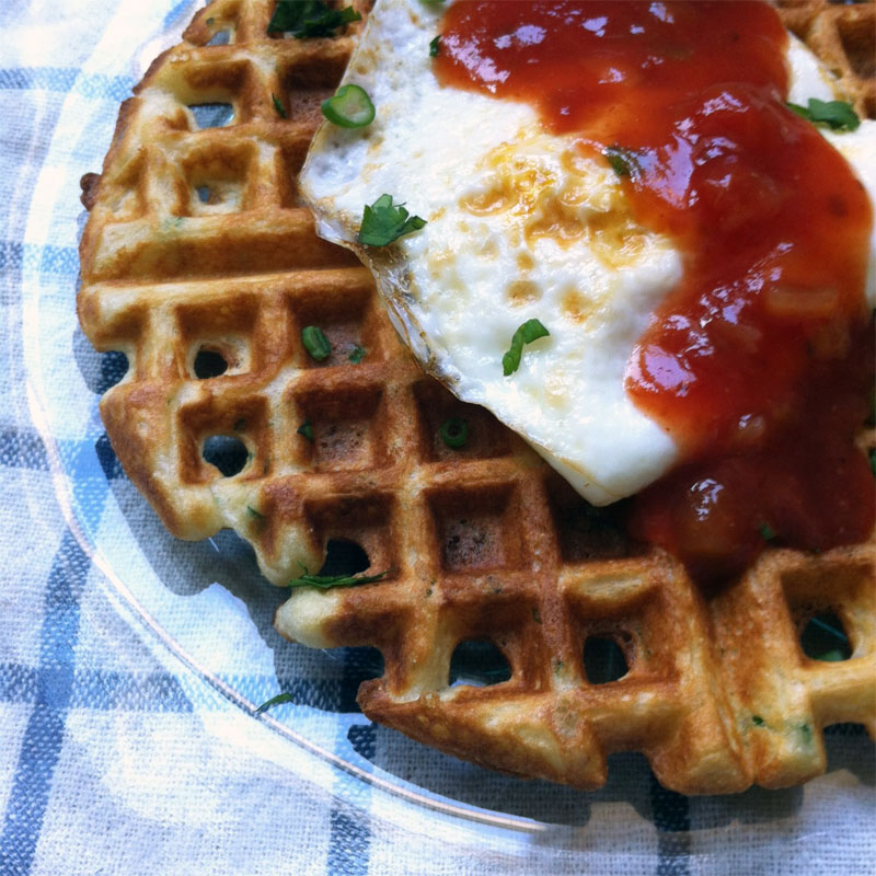 close up of savory chive waffles with salsa and egg