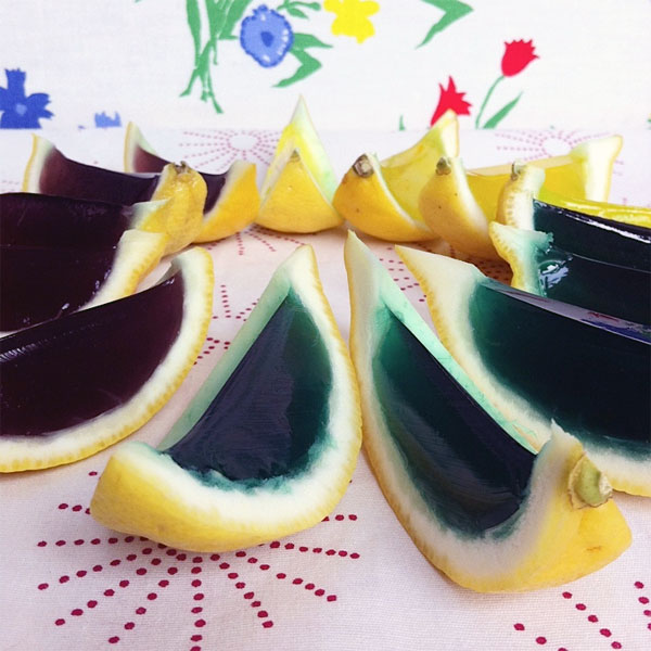 dyed margarita jello shots in lemon wedges