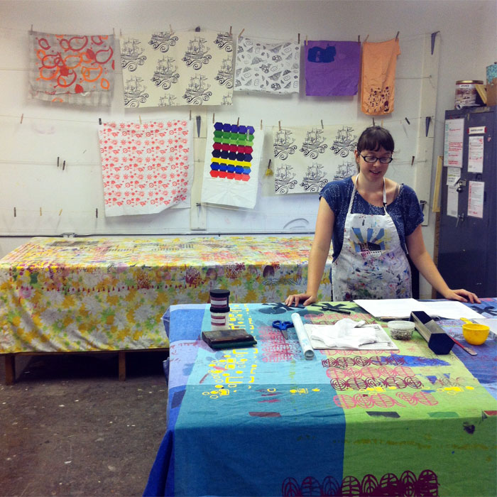 fiber artist Nora Renick Rinehart demonstrating how to screenprint a onesie